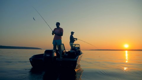 Men are catching fish from an autoboat in the open water