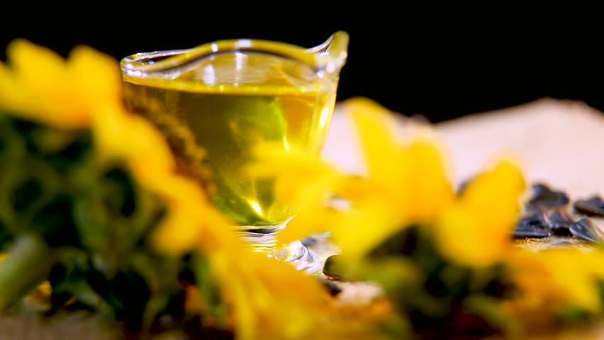 Sunflower oil. Yellow sunflower oil in a transparent glass bowl shines and overflows. Background of sunflower flowers