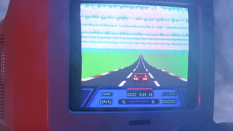 MONTREAL, CANADA - September 2018 : Vintage racing arcade video game on an old tube TV screen. Zooming out with fog giving a retro look at the scene.
