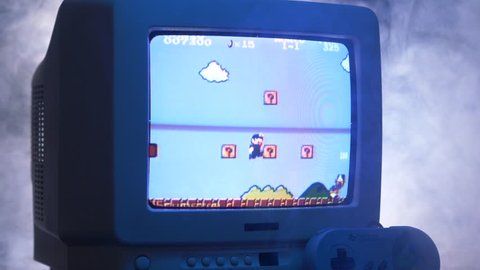 MONTREAL, CANADA - September 2018 : Vintage Nintendo mario bros arcade video game on an old tube TV screen.Zooming out with fog giving a retro look at the scene.