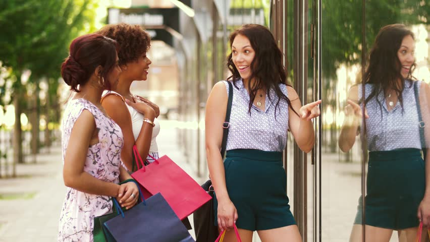 Sale, consumerism and people concept - happy young women with shopping bags pointing finger to shop window in city | Shutterstock HD Video #1015911475
