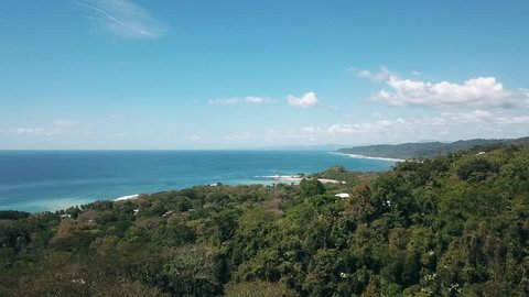 Drone shot of the beach of mal pais, costa rica, coming from the jungle towards the ocean. bright day, blue skies.