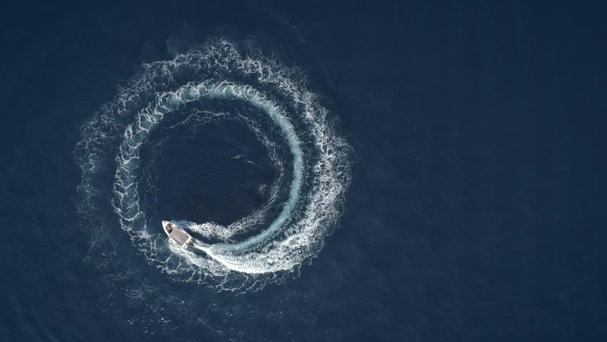 Aerial view of a boat driving in circles forming waves around in Greece. | Shutterstock HD Video #1015977835