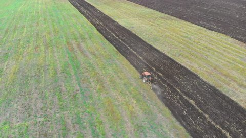 Tractor plowing fields, preparing land for sowing. Aerial view. Farmer in tractor preparing land with seedbed cultivator in farmlands. Tractor plows a field. Agriculture industry, cultivation of land