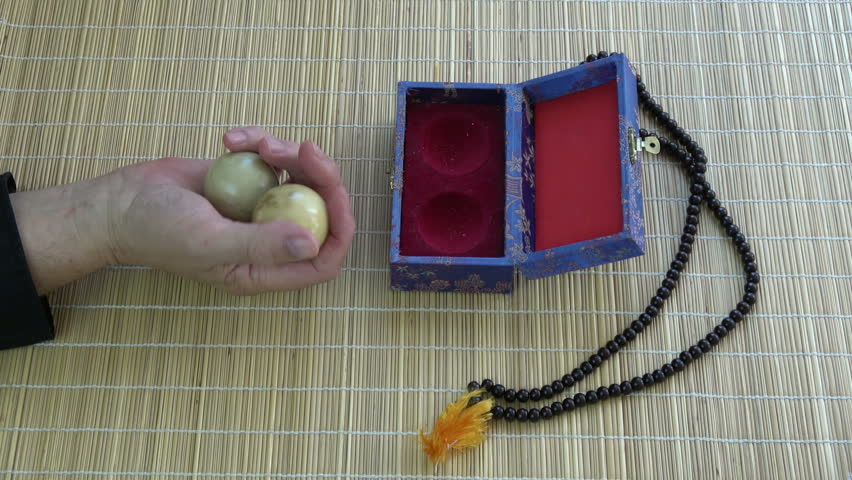 Asian chinese hand massage marble balls in hand  and Buddhist rosary on bamboo mat