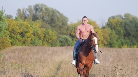 Athletic man with a pumped body rides a horse across the field towards the camera