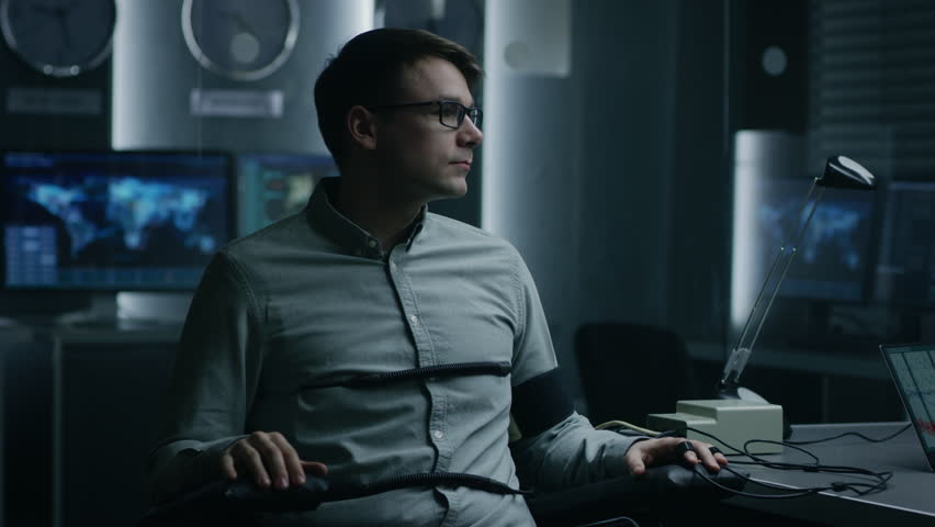 Young Handsome Suspect During Interrogation Undergoes Lie Detector / Polygraph Test, Connected to the Machine He Answers Yer or No Questions. Shot on RED EPIC-W 8K Helium Cinema Camera.