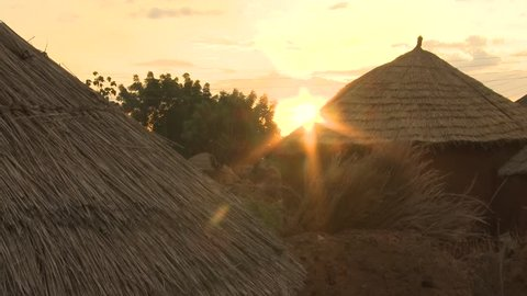 African village of huts and earth houses during sunset.