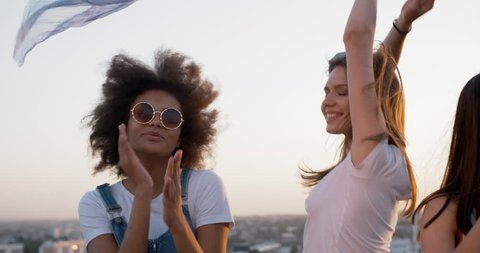 Three young female friends having a summer rooftop party, dancing to music with white shawl closeup 4k