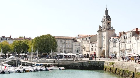 City centre of La rochelle, a seaport on the Atlantic coast in western France. It's a street near the old port. Filmed during the summer. There is boats in the old port of the town.