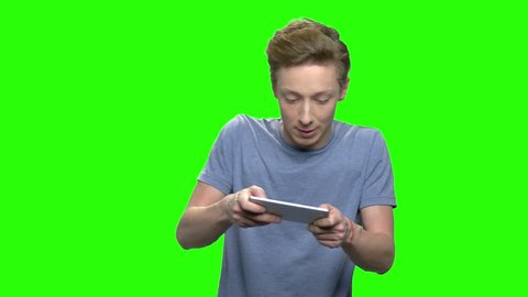 Teenage boy plays games on mobile phone. Emotional excited boy with smartphone. Green screen hromakey background for keying.