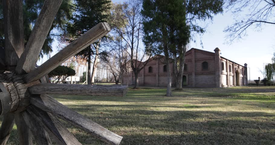 Traveling and panning perfect camera motion of big brick construction at sunset golden hour. Old wooden vintage cart wagon wheel. Trees, leaves and grass. Cellar for wine production in Mendoza, Argent