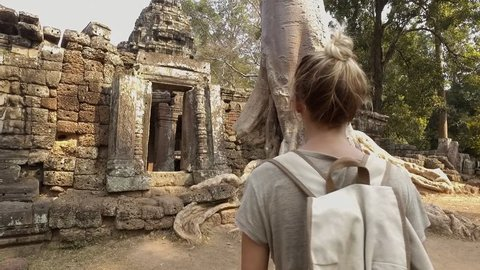 Young woman contemplating ancient temple, travel discovery adventure concept in tropical vacations; blond hair tourist female visiting old ruins Angkor Wat, Cambodia