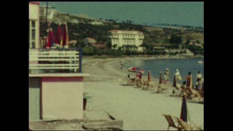 Beach with sunbathers and parasols in Calvi, Corse, France, 1950's. Vintage movie. 8mm film.