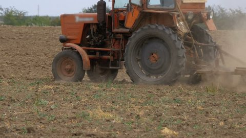 Old tractor plowing field. Farmer plowing the field, close-up. The old rusty tractor preparing land for sowing.