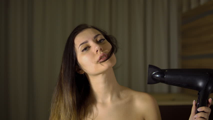 Young beautiful girl dries hair with a hair dryer
