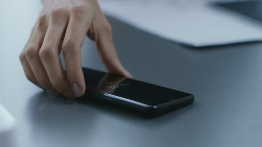 Out of Focus Shot of the Businesswoman Working at Her Office Desk Reaching Out for Her Smartphone and Starts Using It. Woman Picks up Mobile Phone from Her Desk. Focus on a Phone.Shot on RED EPIC-W 8K