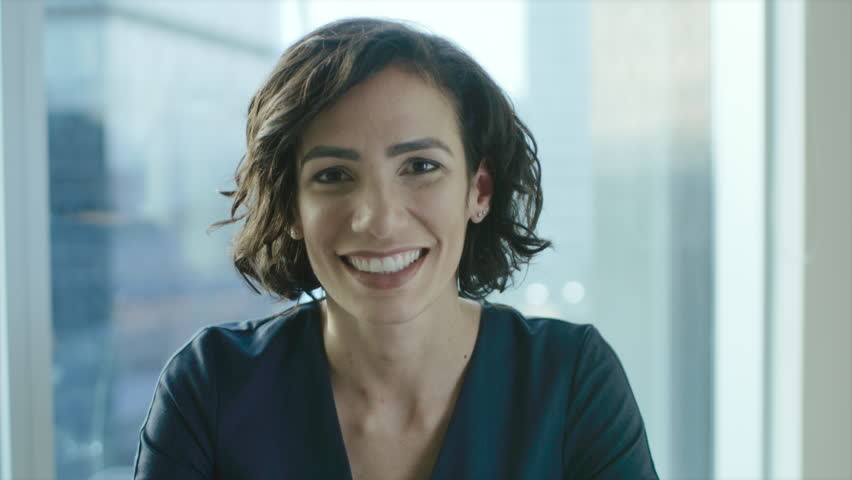 Portrait of a Beautiful Hispanic Woman Smiling Charmingly. Out of Focus Cityscape Background. Shot on RED EPIC-W 8K Helium Cinema Camera. | Shutterstock HD Video #1016145895