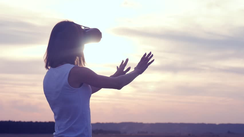 Girl in virtual reality goggles in field on sunset. Woman looking at virtual reality glasses at sun. | Shutterstock HD Video #1016149555