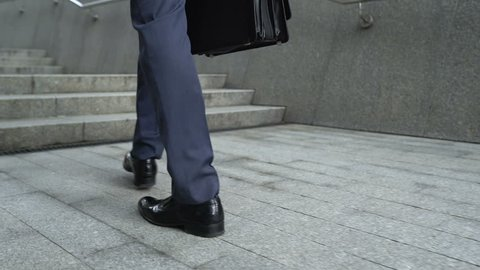 Closeup of businessman climbing stairs, concept of success in career, promotion
