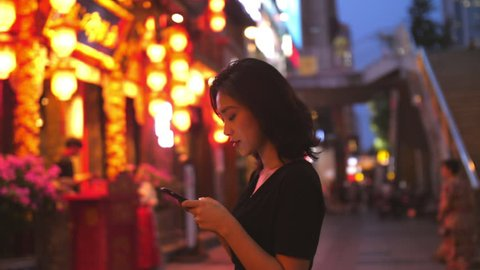 Young Chinese woman using mobile phone in street with traditional Chinese style building red lantern in the background in slow motion at Chengdu Sichuan China city