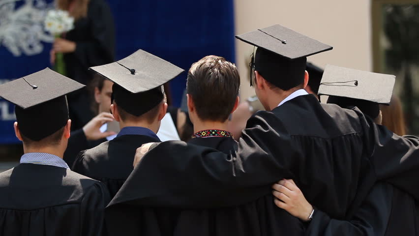 University friends hugging, posing for picture together, graduation ceremony