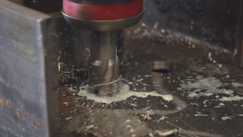 Workers are using a steel drill, with pouring coolant on a drill. Slow motion