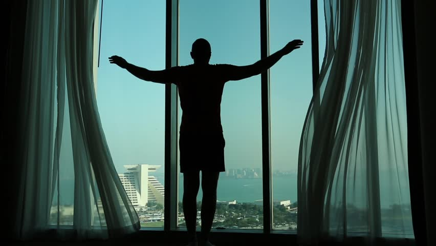 Man opens big window curtains. Man opens curtains in morning, raises his hands and stretch oneself. View of Doha - capital and most populous city in Qatar, Persian Gulf, Arabian Peninsula, Middle East