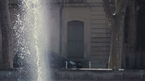 fountain in the foreground, fixed shot, road at the background, slow motion foutain, cars in the background,