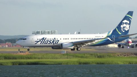 Alaska Airlines jet plane taxies to runway for take off, Boston Harbor waters edge, Logan Airport Boston Massachusetts USA, July 5, 2018