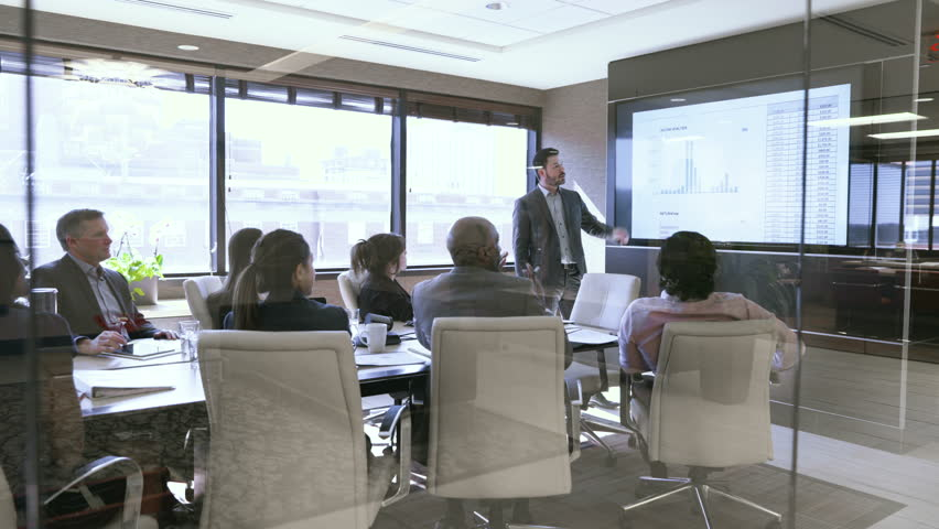 Dolly shot of business people in meeting at board room seen through glass | Shutterstock HD Video #1016241475