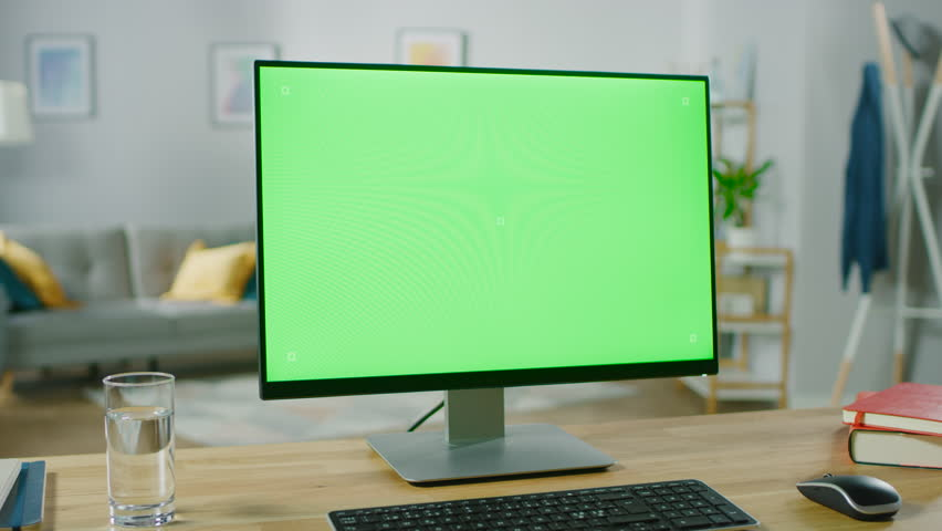 Modern Personal Computer with Green Mock-up Screen Display Standing on the Desk in the Cozy Living Room. A Man with Mobile Phone Walks Through His Flat. Shot on RED EPIC-W 8K Helium Cinema Camera. | Shutterstock HD Video #1016261905