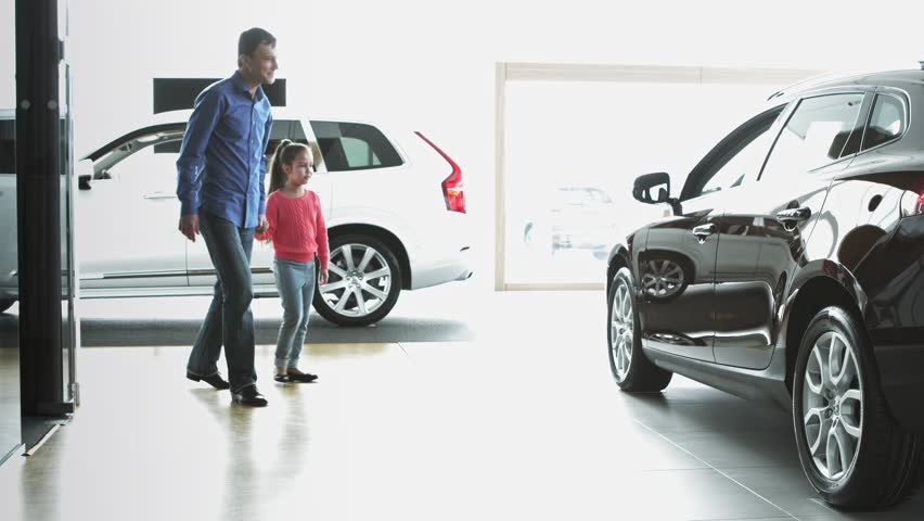 Dad with daughter are looking on the new car. They are in car dealership. | Shutterstock HD Video #1016286625