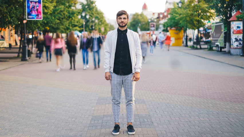 Time-lapse of handsome young man in stylish clothing standing in the street of big city and looking at camera with people moving around. Urban lifestyle and society concept. | Shutterstock HD Video #1016310265