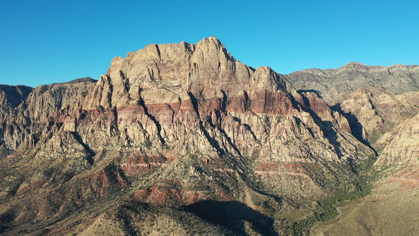 Early light shines on the Red Rock Canyon National Conservation Area, located just outside of Las Vegas, NV. Its massive red rock geologic formations are popular for hiking and climbing.   Shutterstock HD Video #1016317735
