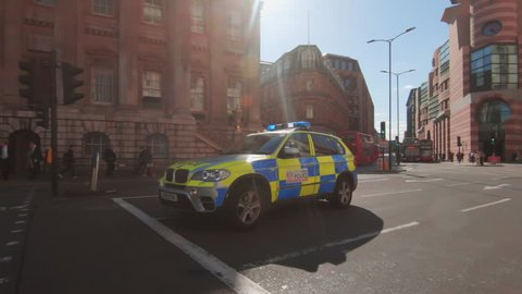 LONDON, UK - SEP 13, 2018: Camera pans to follow speeding police car by Bank Station in the financial disrict of the city