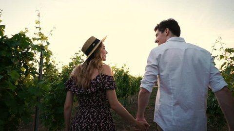 Young happy loving couple walking outdoors in the vineyard talking with each other