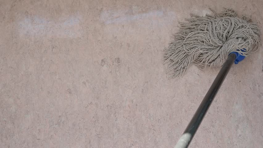 point-of-view of cotton mop cleans a shiny wet pink linoleum floor