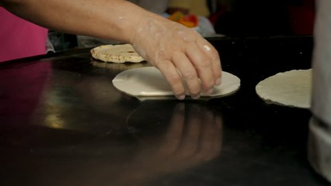 Close up of a woman's hand flipping a handmade corn tortilla on a metal pan or comal