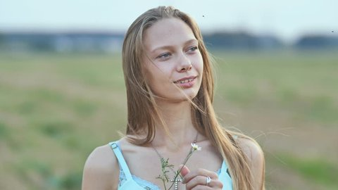 Portrait of a young smiling sixteen-year-old girl with a daisy flower in her hands. Blonde with long hair.