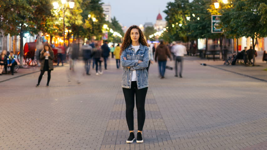 Zoom in time-lapse of stylish young lady tired of usual haste standing in the street among whizzing people and looking at camera. Time, youth and society concept.