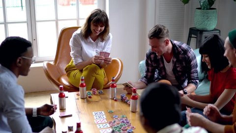 Joyful male and female friends sitting at table in modern living room resting together and playing games on cards, smiling teen hipster guys communicating and gambling during weekends recreation