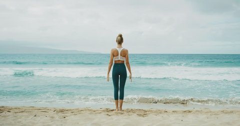 Fitness lifestyle of beautiful young woman stretching and practicing yoga at the beach