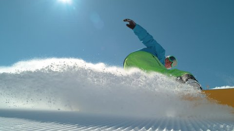 SLOW MOTION CLOSE UP: Extreme snowboarder carving downhill and spraying snow into camera. Smiling active man snowboarding on groomed ski slope in mountain resort. Cheerful snowboarder turning