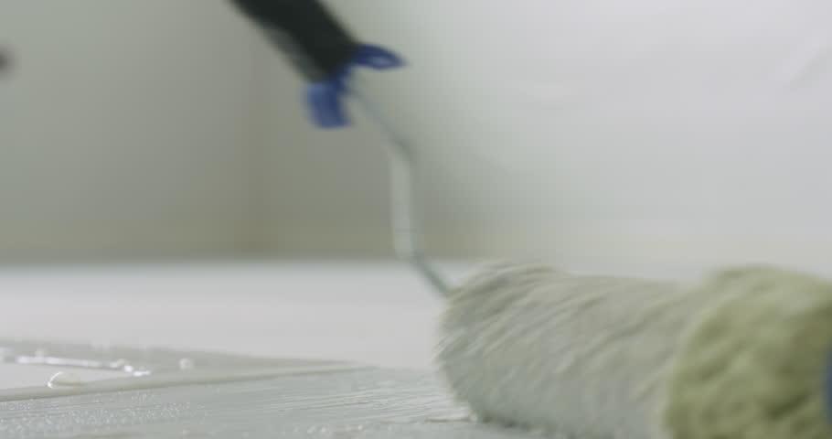 Slow motion closeup applying primer on the floor