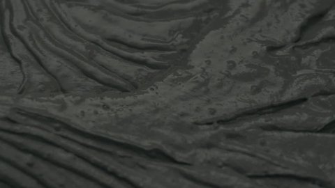 Slow motion closeup mixing dark gray micro concrete plaster