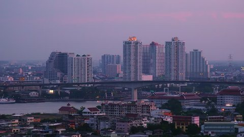 Gorgeous panoramic view of Bangkok at dusk. Fantastic cityscape with beautiful buildings with electric light in windows and Rama III bridge crossing Chao Phraya River. Modern Asian city in evening.