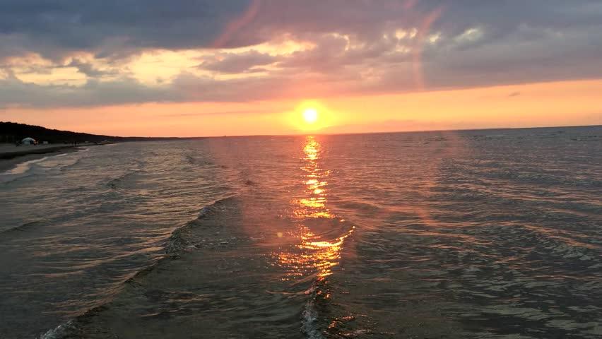 Sunset sea, swimming people (silhouettes).  Waves, Baltic sea, sunset sky.