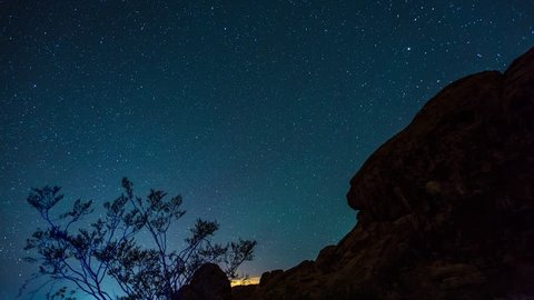 Motion timelapse of the night sky and milky way over red rocks in Valley of Fire State Park, Nevada