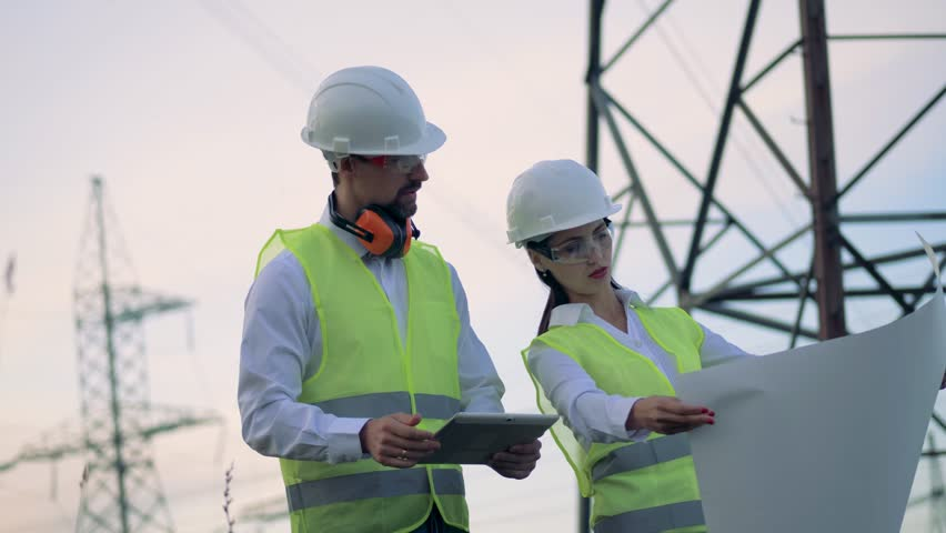 Electricians, engineers looking at a blueprint, close up.